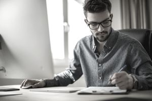 Young man in glasses makes handwritten notes at desk