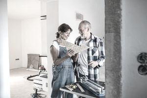 Older couple looking at tile flooring amid a home renovation.