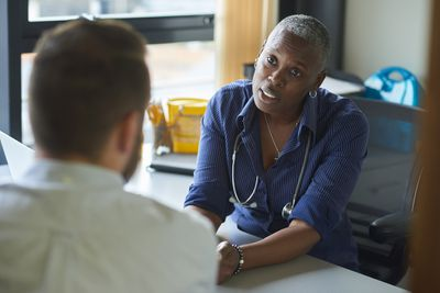 Physician with stethoscope listens intently to patient speaking