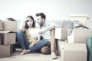 Worried couple reading paperwork in a new home surrounded by boxes