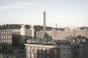 A brick factory building with a smokestack is highlighted by a sunset