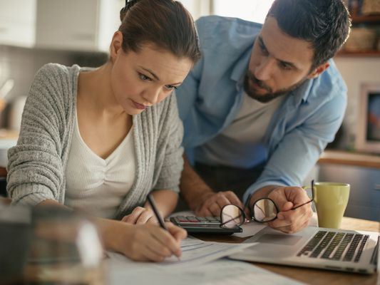 Worried couple working at kitchen table paying bills when money is tight.