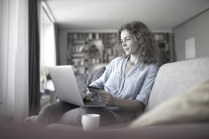 Smiling woman doing online shopping on laptop at home