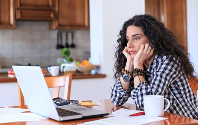 Woman With Checked Shirt and Dark Curly Hair Staring Into a Laptop Screen in a Kitchen.