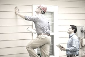 Repairmen, building inspectors, exterminators, engineers, insurance adjusters, or other blue collar workers examine a building/home's exterior wall and foundation. One wears a red hard hat and clear safety glasses and holds a clipboard. The other holds a digital tablet.