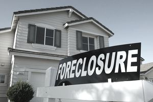 a home with a foreclosure sin in front of it