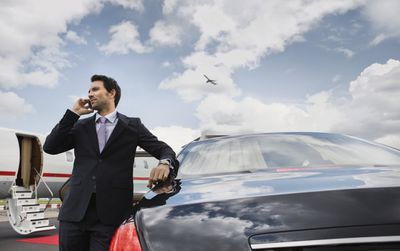 Businessman on a cellphone next to a car near a private jet at an airport