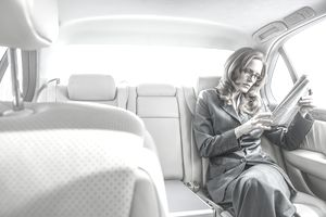 Businesswoman reading newspaper in car