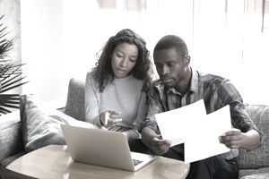 A couple reviews documents while sitting in front of a laptop