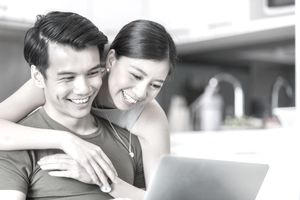 A young couple smile as they look at a computer screen together