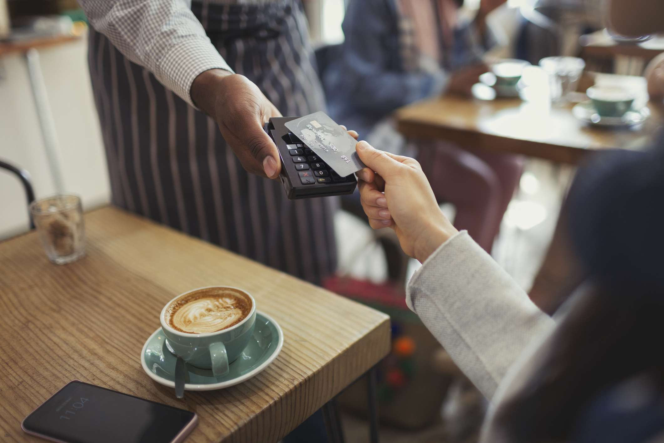 Person handing credit card to a server