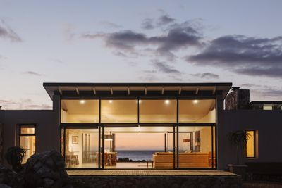 Illuminated luxury home with glass wall under sky at dusk