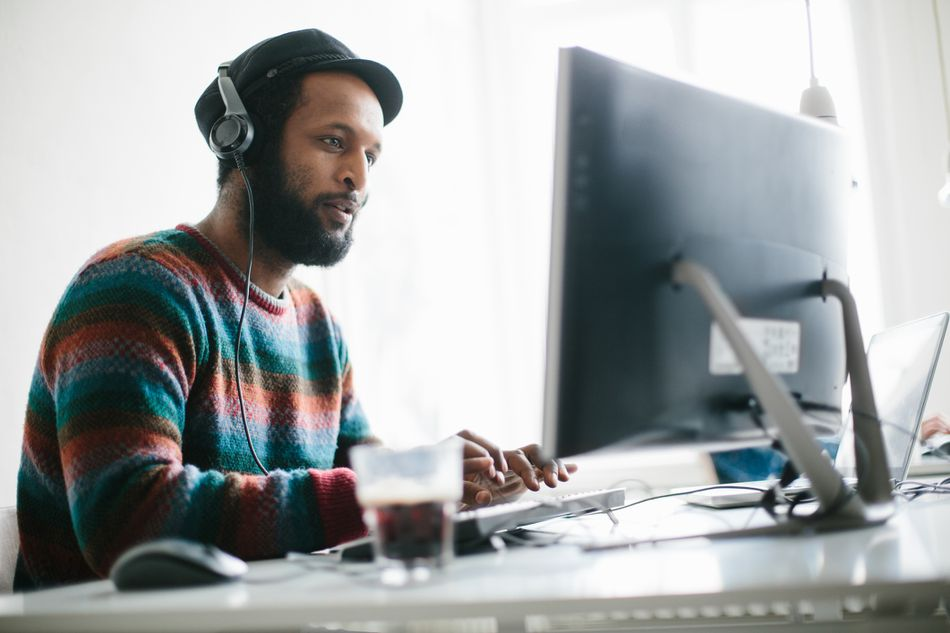Man on computer with headphones