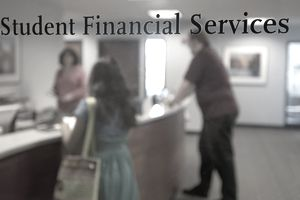 Two students inside the Northeastern University Student Financial Aid Office wait for help from an advisor