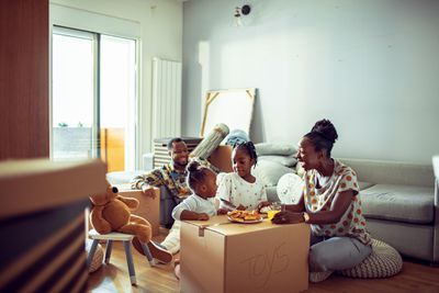 Parents and two young daughters eat breakfast on moving boxes
