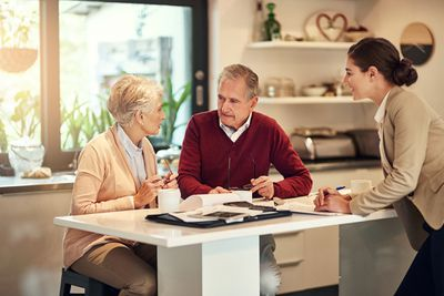 Couple talking to a financial advisor about when they should take social security.