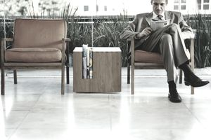 Man reading a finance magazine while waiting in a sitting area.