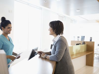 Patient paying insurance copayment to nurse with credit card at clinic check-in counter
