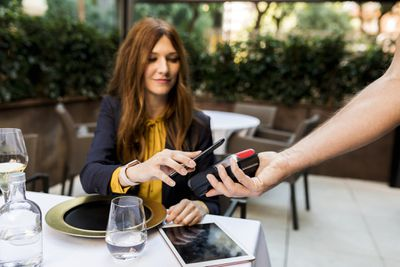 Woman paying with smartphone in a restaurant.