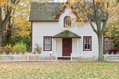 Home with trees and a white picket fence around it