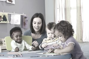 A childcare provider at table with three children coloring