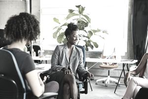 Smiling businesswoman leading team discussion at workstation in design office