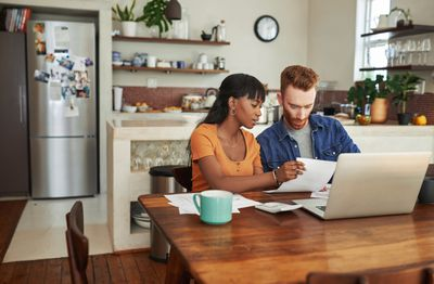 Couple handles paperwork in front of a laptop while sitting at their kitchen table