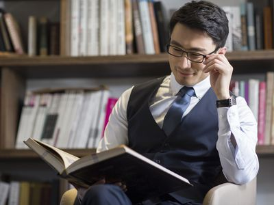 Man with glasses in a dress shirt, tie, and vest reading a book
