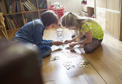Two children counting coins together on the floor