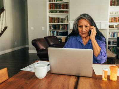 A woman sits at her kitchen table while paying medical bills, talking with her doctor, and updating medicine prescriptions.