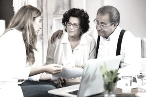 An elderly couple site grimly side-by-side while they review estate planning options with an attorney.