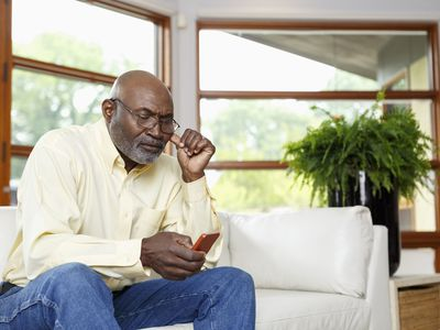 Man sits on coach and reads phone looking concerned