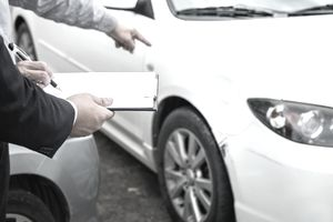 Midsection Of Owner Pointing Towards Car While Signing Paper With Agent