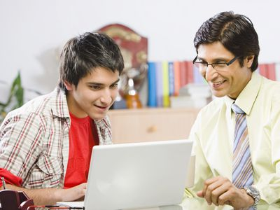 Father and son looking at the FAFSA website on a laptop