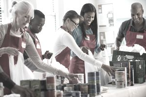 Volunteers at a food bank fill bags with groceries, which were probably purchased with a credit card.