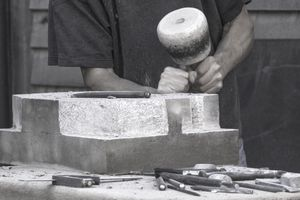Stone mason carving stone with mallet and chisel