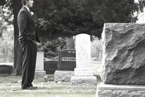 man in a suit at a cemetery at a gravesite