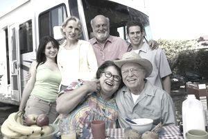 Family posing together over breakfast outside an RV