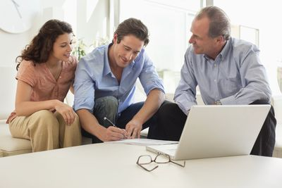 Couple reviewing and signing papers with businessman