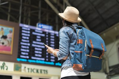 A backpacking young woman tourist looks up at the overhead flight info board in an airport terminal.