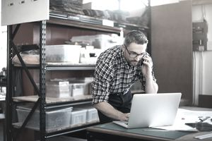 Bespectacled man working on a laptop while talking on phone