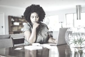 Woman looking concerned while paying bills from home.