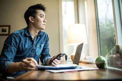 A young man reviews his investments using a laptop.