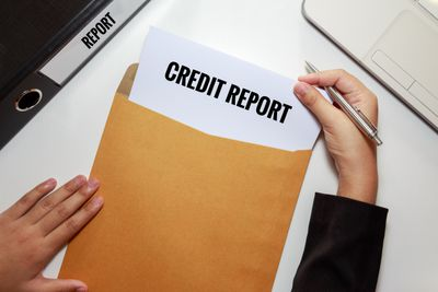 Hands Removing Paper Credit Report From Envelope At Table