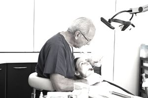 Woman with dental insurance getting her teeth examined by her dentist