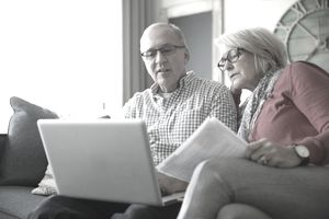 Senior couple with paperwork using laptop on living room sofa
