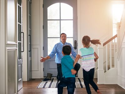 Father greeting his children with open arms as they run to him at the front door