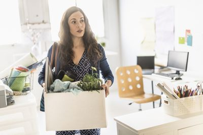 Businesswoman carrying cardboard box out of office