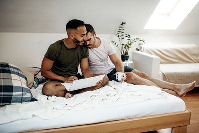 Young male couple on bed with laptop in bright studio