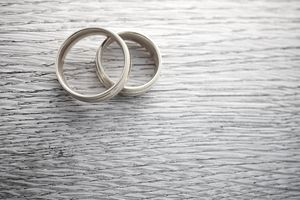 A pair of gold wedding rings symbolize marriage which is a qualifying life event for insurance